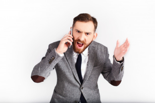 Angry-man-in-grey-suit-talks-on-the-phone_8353-1253