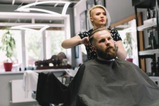 Parrucchiere-alla-moda-taglio-dei-capelli-del-cliente-al-negozio-di-barbiere_1429-4446